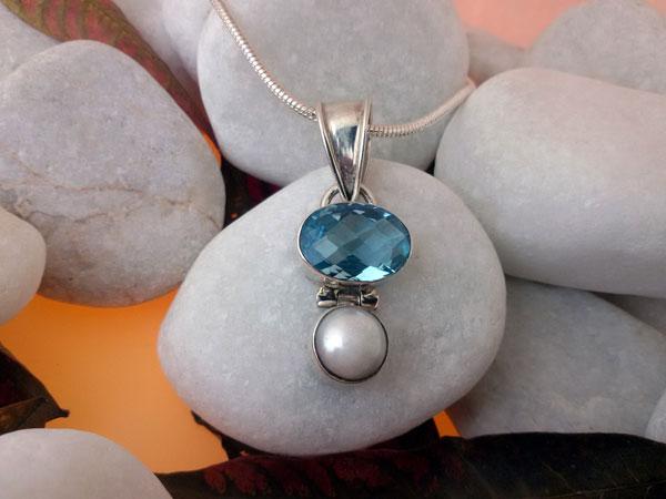 Colgante artesanal de plata y un conjunto de Topacio azul facetatado con una perla natural.. Ref. ERX
